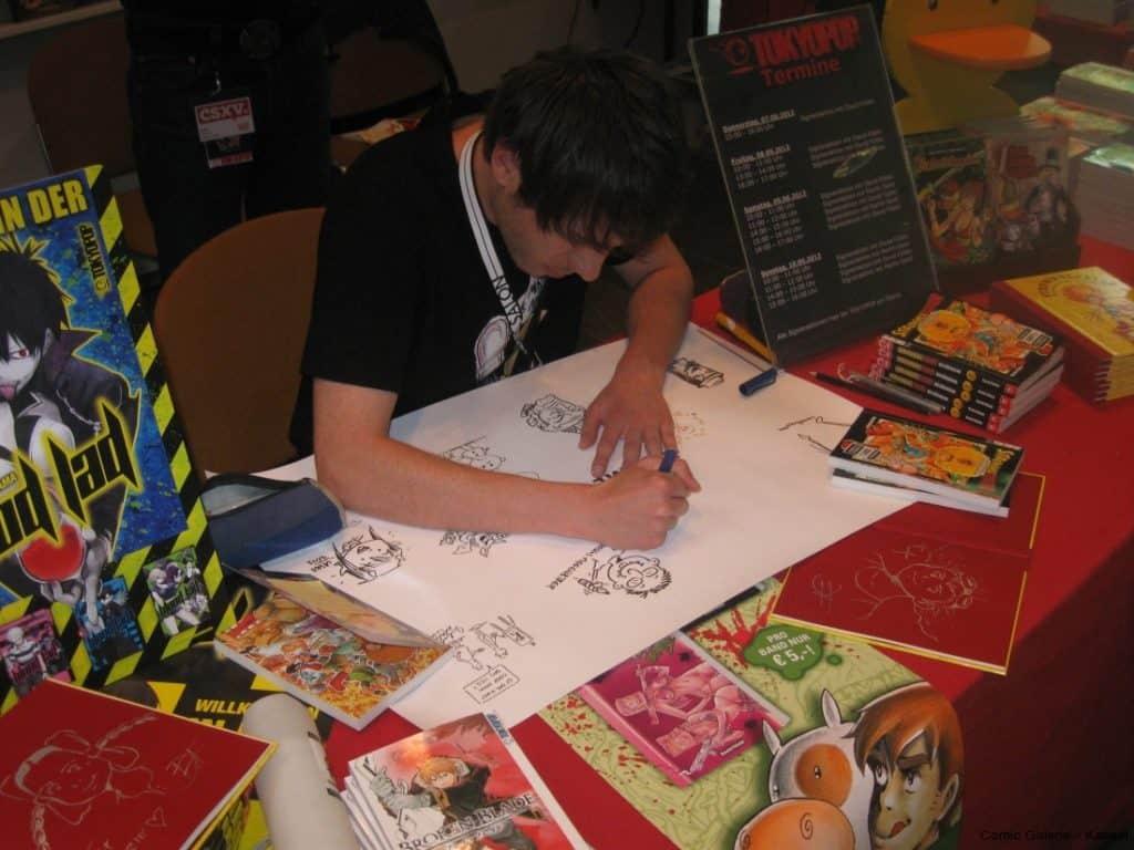 David Füleki beim zeichnen auf das dOKUMENTA (13) Bild der Comic-Galerie.